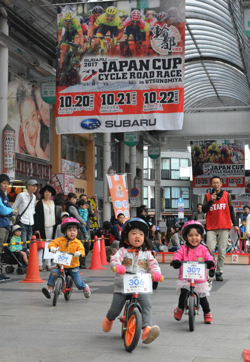 ジャパンカップのビッグフラッグがたなびくオリオン通りを走る子どもたち
