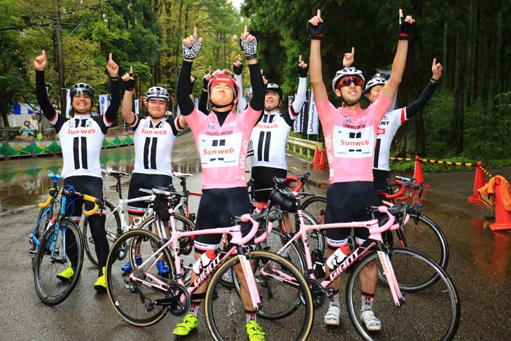 天を指差すワレン・バルギルのポーズで決めるサンウェブのコスプレ6人衆。2人のバイクはピンクのジロ優勝記念車