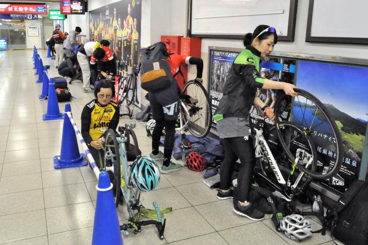 駅構内で愛車を組み立てる輪行の乗客たち