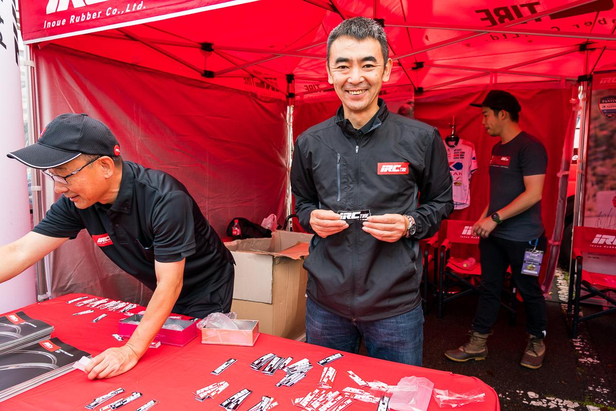 IRCタイヤのステッカー配布コーナーにはチームユーラシアIRCタイヤの橋川健監督が登場