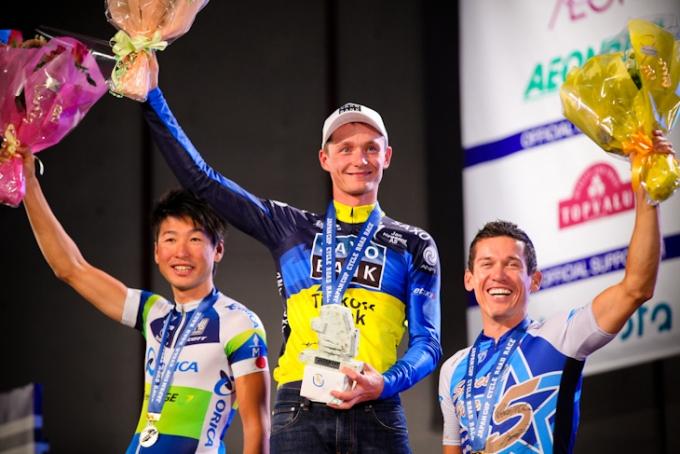 2012年ジャパンカップクリテリウムの表彰台に登る別府史之、マリチ、マキュアン